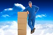 Happy delivery man leaning on pile of cardboard boxes against bright blue sky with clouds