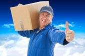 Happy delivery man holding cardboard box against bright blue sky over clouds