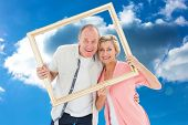 Older couple smiling at camera through picture frame against cloudy sky