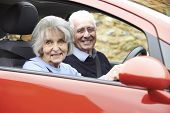 Portrait Of Smiling Senior Couple Out For Drive In Car