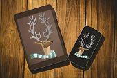hipster reindeer against tablet and smartphone on desk