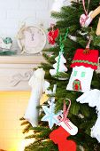 Christmas handmade decorations on Christmas tree  on light home interior background