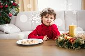 Festive little boy having milk and cookies against hanging decorations