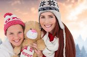 Mother and daughter with teddy against blurred fir tree forest
