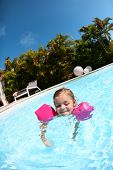 Cheerful little girl in swimming-pool