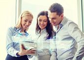business and office concept - smiling business team working with tablet pc in office