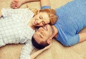 love, family and happiness concept - smiling happy couple lying on floor at home