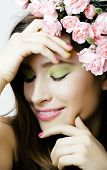 Beauty young real woman with pink flowers and make up closeup