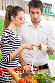 pic of receipt  - Young couple at supermarket checking a long receipt with shopping cart on foreground - JPG