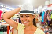 Pretty Girl Tries On A White Hat In The Store