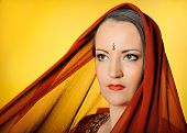 Young Beautiful Woman In Indian Traditional Jewellary, Bindi And Sari Dress Covered In Veil. Yellow