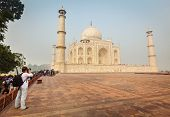 AGRA, INDIA - NOVEMBER 17, 2012: Tourist takes pictures of Taj Mahal - famous Indian landmark and tourist attraction - UNESCO World Heritage Site is considered one of most beautiful buildings in world