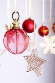 Beautiful red Christmas decorations hanging on light blurred background