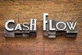 cash flow words in mixed vintage metal type printing blocks over grunge wood