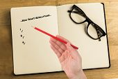 Composite image of new years resolutions against overhead of reading glasses with notebook