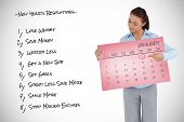 Young businesswoman looking at the calendar she is presenting against pink card