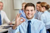 business, people, gesture and teamwork concept - smiling businessman showing ok gesture with group of businesspeople meeting in office