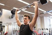 sport, bodybuilding, lifestyle and people concept - young man with barbell flexing muscles in gym