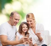 family, summer, technology and people concept - smiling mother, father and little girl with smartphones over green background