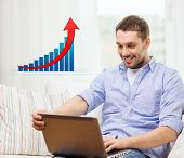 people, technology, statistics and business concept - smiling man with laptop computer and growth chart sitting on sofa at home