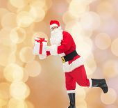 christmas, holidays and people concept - man in costume of santa claus running with gift box over beige lights background