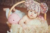 The newborn girl in a knitted hat lying in a basket.