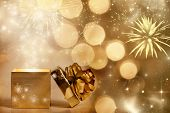Christmas background with gift box over sparkling background and fireworks
