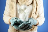 Knitted Christmas angel in female hand on color background