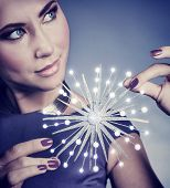 Closeup portrait of gorgeous female with beautiful festive makeup holding in hands glowing snowflake, luxury Christmas accessories