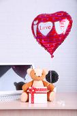 Teddy bear with present box, plant and love heart balloon on wooden  computer table, on the brick wall background