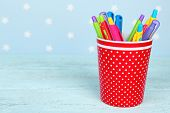 Plastic cup with different pens on color wooden table on color wooden table and blue background with printed stars
