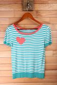 Female t-shirt on hanger on wooden wall background