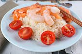 Boiled rice and shrimps, salmon on plate, on wooden background