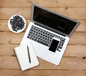 Open notebook, diary and smart phone with saucer of candies on wooden background, top view