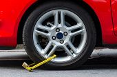 pic of illegal  - Clamped wheel of illegally parked red car - JPG
