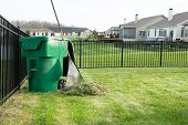picture of neat  - Raking lawn clippings on a neat upmarket suburban housing estate with a heap of grass cutting alongside a rake leaning on a green plastic bin for composting organic waste - JPG