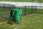 stock photo of neat  - Yard maintenance in spring with a fresh heap of grass clippings and a rake leaning on a green plastic bin for composting organic waste on a neat lawn with wrought iron fence above a lake - JPG