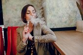 image of electronic cigarette  - beautiful elegant young woman smoking electronic cigarette - JPG