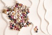 foto of agate  - Conceptual map of France and Corsica formed of colorful waterwashed pebbles of quartzite agate jasper and dolomite on white bach sand with an undulating wavy pattern - JPG