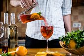 image of sangria  - Man pours homemade sangria with fruit pieces in a glass - JPG