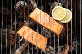 foto of flame-grilled  - Top view grilled salmon with lemon on the flaming grill - JPG