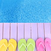 stock photo of beside  - Female flip flops on wooden platform beside sea - JPG