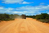 stock photo of loamy  - Back view of a safari vehicle for tourists driving a road between the bushes towards the blue sky in a game park in South Africa - JPG