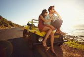 foto of road trip  - Relaxed young couple sitting on the hood of their car alongside a open coastal road with man answering a phone call and woman sitting by - JPG