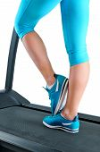 picture of treadmill  - Female legs in turquoise sneakers on a treadmill - JPG
