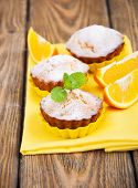 image of bakeshop  - Homemade Muffins Ready for Breakfast with orange slices on a napkin on wooden background - JPG