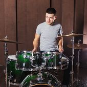 pic of drum-kit  - Handsome guy behind the drum kit on a brown background - JPG