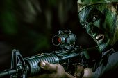 foto of special forces  - A soldier in war paint looks through the scope of automatic rifles - JPG