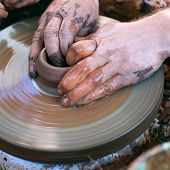 picture of molding clay  - Hands working with clay on pottery wheel - JPG