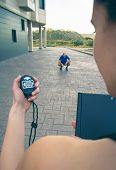 picture of chronometer  - Closeup of woman trainer hand using a chronometer to timing at tired athletic man in a hard training outdoors - JPG